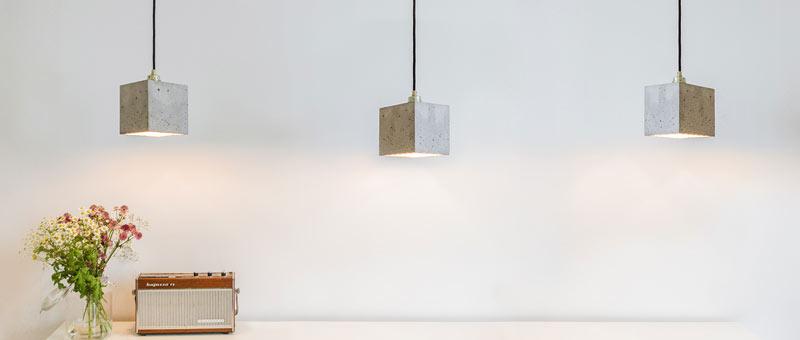 Betonlampe über Tisch, hellgrau innen Gold