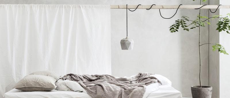 Betonlampe über Massivholz Bett